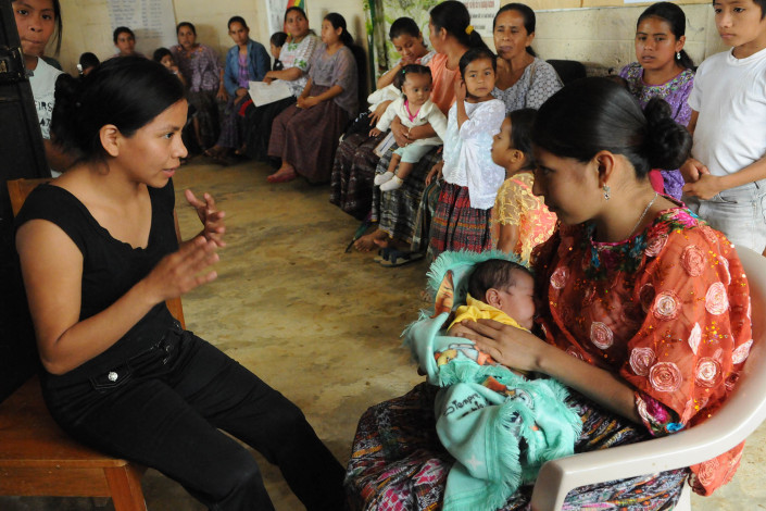 A health worker consults with a Mayan woman who is breastfeeding her 3-month-old daughter, in a rural health center in Guatemala.