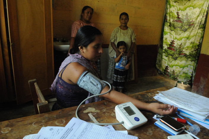 An indigenous Mayan woman, 7 months pregnant, has her blood pressure monitored at a rural health center in Guatemala.