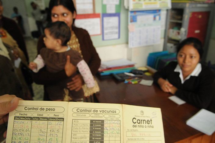A health worker holds the immunization card of a 7-month-old child at a health center in Guatemala.