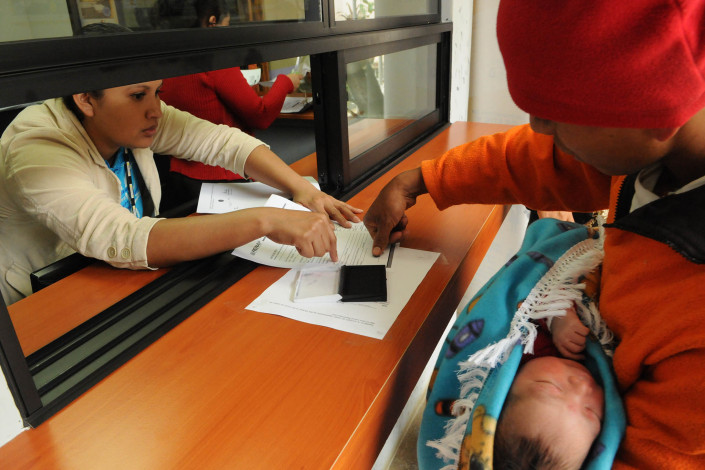 A health worker assists an indigenous Mayan man, holding his newborn son, as he puts his thumbprint on birth registration papers in Guatemala.