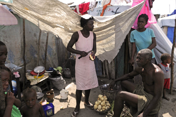 A family prepares a midday meal in their makeshift home at Carrefour Aviation, a tent camp housing 50,000 people who were displaced by the quake.By late June 2010 in Haiti.