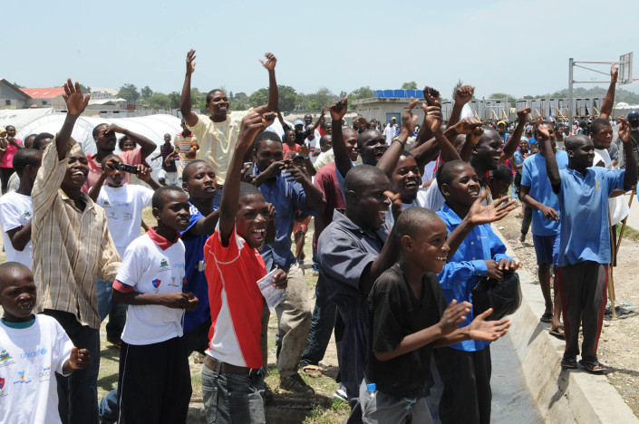A group of men and adolescent boys greet footballer Leo Messi, at Carrefour Aviation, Port-au-Price, Haiti.