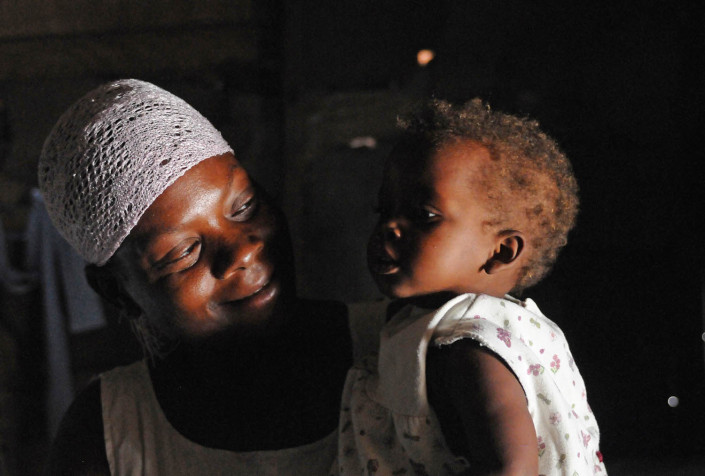 A woman holds her 13-month-old daughter, inside their makeshift home at Carrefour Aviation, a tent camp in Port-au-Prince, housing 50,000 people displaced by the January 2010 earthquake that killed more than 225,000 and displaced more than two million people.