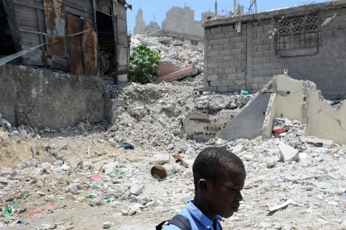 A boy walks to school past homes devastated by the 7.3 magnitude earthquake which took place on 12 January 2010, in Port-au-Prince, Haiti.