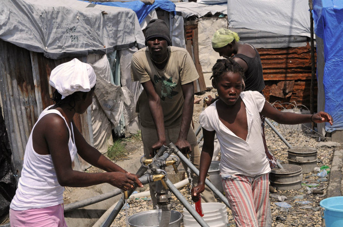 A girl collects water at Carrefour Aviation, a tent camp housing 50,000 people who were displaced by the 7.3 magnitude earthquake on 12 January in Haiti.