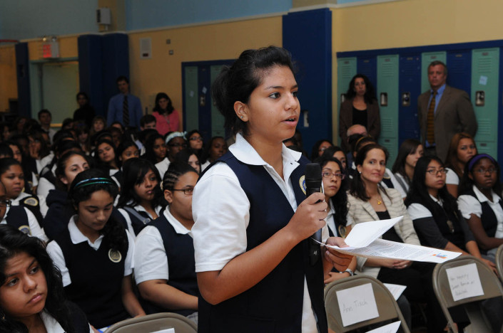 A girl asks a question at a school assembly in an auditorium.