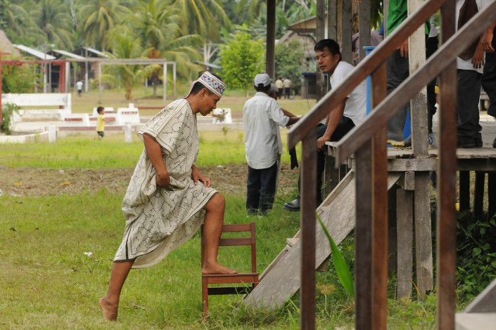 An indigenous Shipibo Conibo man wearing traditional dress walks up stairs to a community center in Nuevo Saposoa in the Peruvian Amazon.
