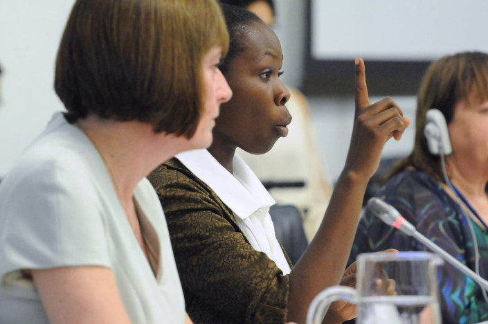 An adolescent girl addresses a meeting in sign language at the UN.