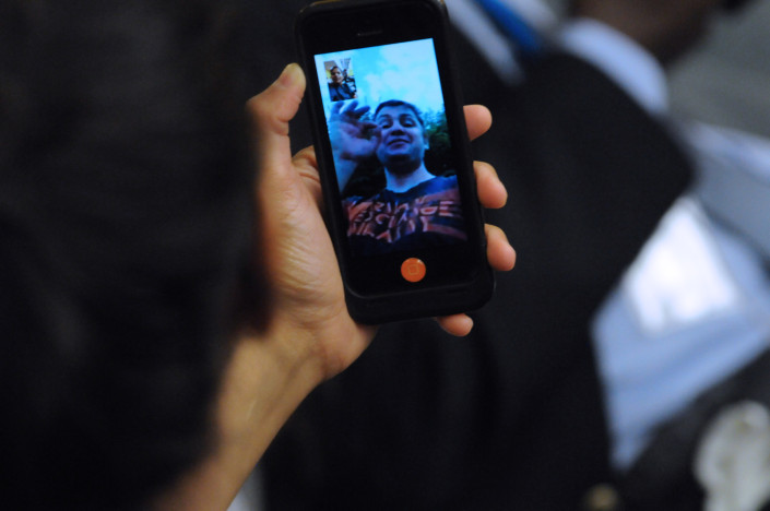 A woman speaks in sign language to a friend on her cell phone on FaceTime.