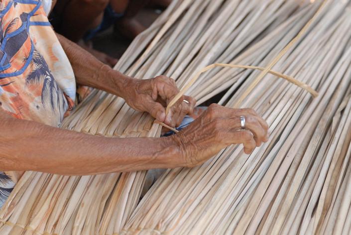 Brigida Paz, an indigenous Añu woman, weaves dried palm leaves in Laguna de Sinamaica, Venezuela.