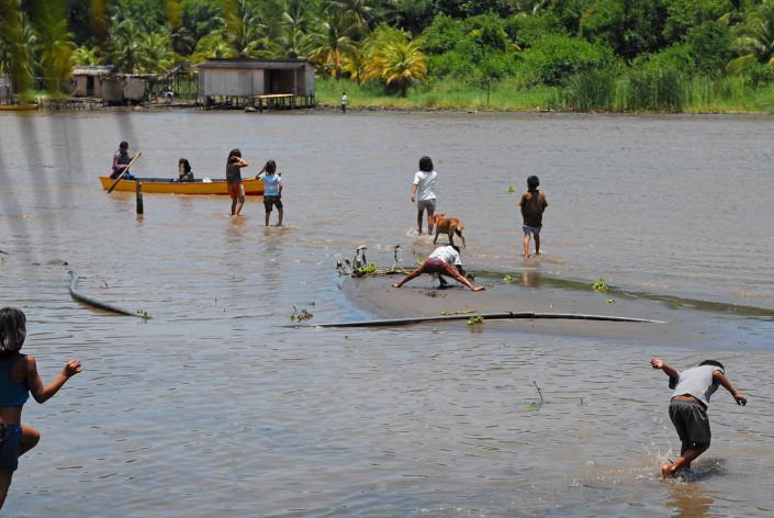 Indigenous Añu children play in a lagoon beneath their homes, in Laguna de Sinamaica, Venezuela.