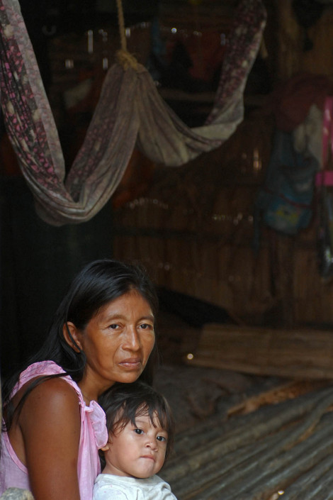 An indigenous Añu woman sits inside her home with her 1-year-old daughter, in Laguna de Sinamaica, Venezuela.