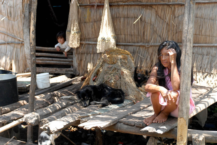 An indigenous Añu woman sits on a makeshift wooden dock outside her home above a lagoon as dogs laze nearby and her daughter leans out of a window, in Laguna de Sinamaica, Venezuela.