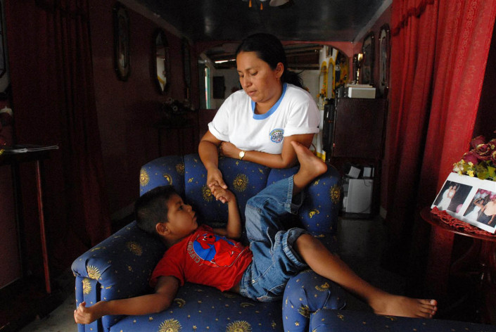 A 5-year-old Añu boy holds his mother's hand, as he tells her a traditional story in their home in Laguna de Sinamaica, Venezuela.