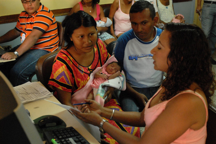 An indigenous Wayuu woman holds her newborn daughter as she and her husband obtain a civil birth registration certificate from a health worker in Maracaibo, Venezuela.