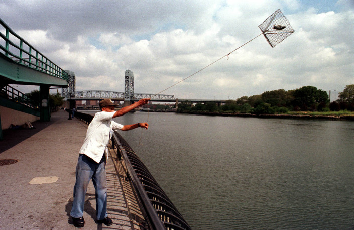 A man throws a crab trap with bait fish, into the East River in NYC.