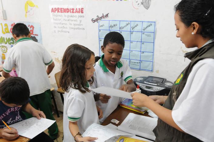 Children hand in schoolwork to their third-grade science teacher in a school in Medillin, Colombia.