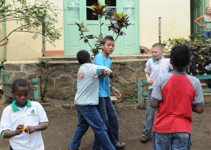 A boy bullies another outside a school in Colombia.