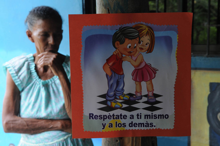 An elderly woman stands behind a sign that says Respect yourself and others, in Spanish, in Colombia .