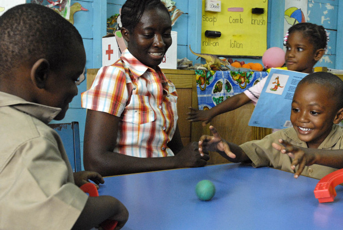 A teacher sits beside young children playing in their classroom n the parish of Kingston and St. Andrew, Jamaica.