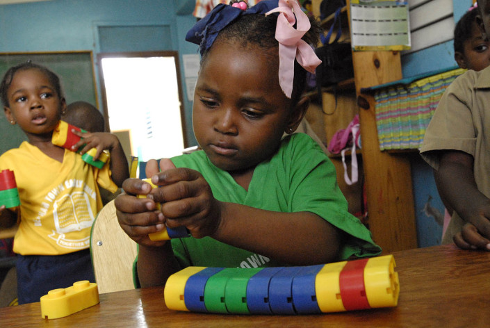 A girl plays with colourful plastic blocks at the UNICEF-supported Denham Town Basic School in the Denham Town community in the parish of Kingston and St. Andrew, Jamaica.