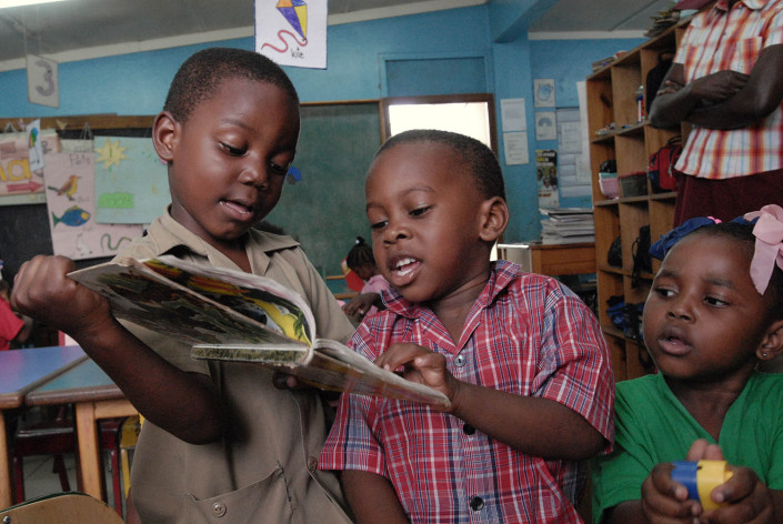 Boys read a book as a girl plays with colourful plastic blocks at a school in the parish of Kingston and St. Andrew, Jamaica.
