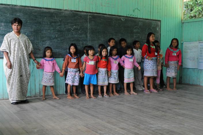 A teacher stands beside his students in the indigenous Shipibo-Conibo community of Nuevo Saposoa in the Peruvian Amazon.