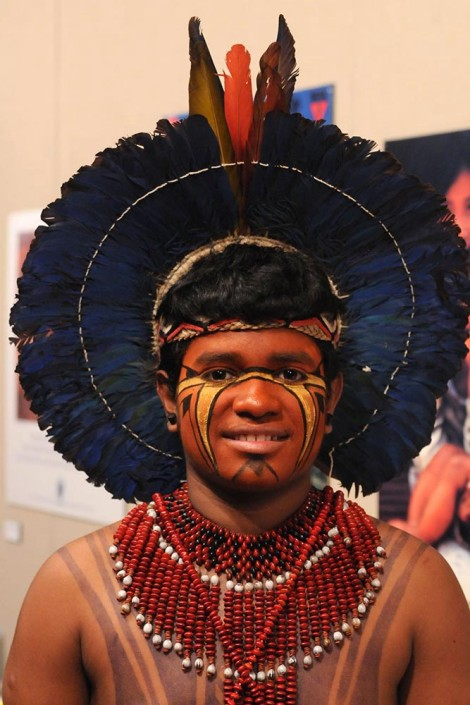 Portrait of an indigenous adolescent boy wearing traditional dress including a headdress with feathers, face paint and a large red and black beaded necklace.