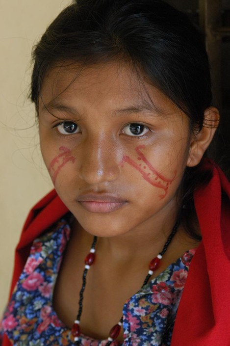 An indigenous 15-year-old-girl in traditional dress and paint, prepares for a traditional dance.