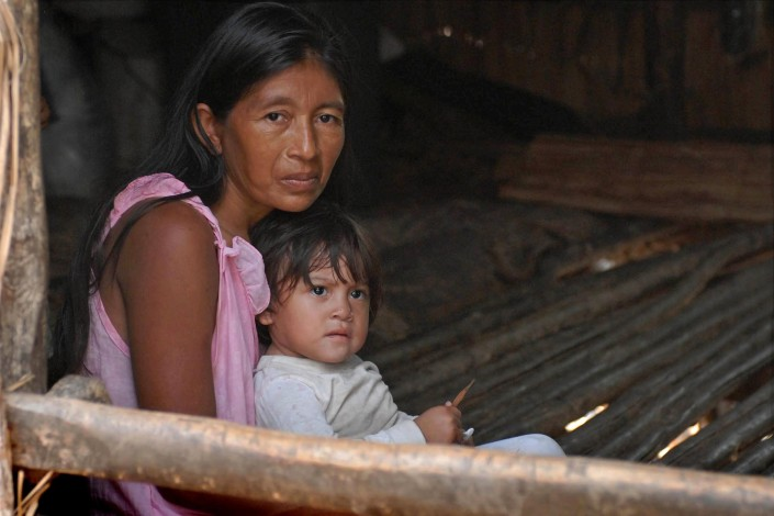 An indigenous Añu woman sits with her 1-year-old daughter in her home made of wooden poles, above a lagoon, in Venezuela.