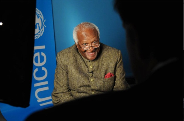 Archbishop Desmond Tutu, smiling, is interviewed in a studio with a UNICEF logo in the background.