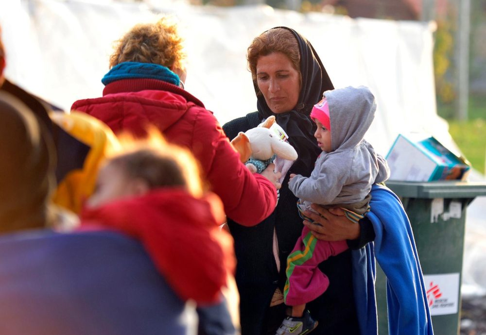 medium.com screen capture of refugee woman holding baby, getting toy from an aide worker.