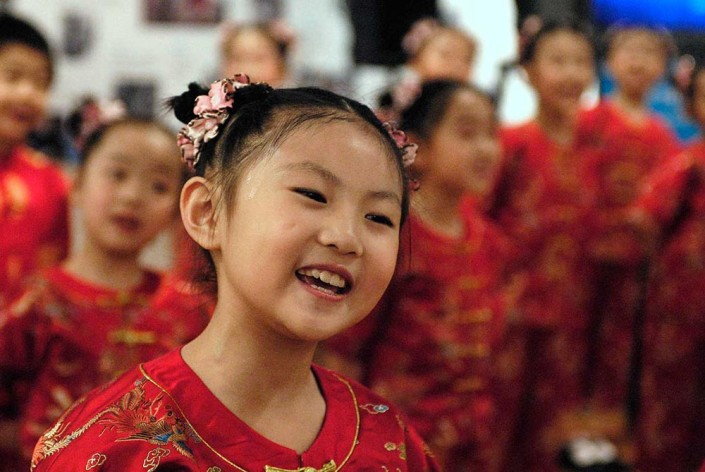 A young Chinese girl dressed in a red satin costume, performs a traditional dance.