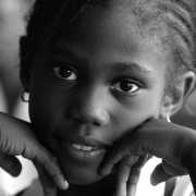 A wide-eyed schoolgirl leans on her hands during a classroom discussion in Jamaica.