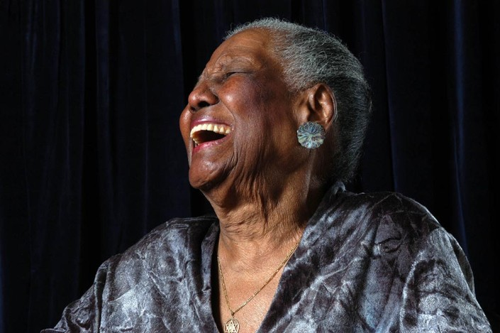 An 86-year-old elegantly-dressed woman, smiles in a hearty laugh with her head thrown back.