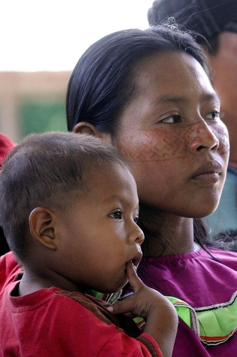 A woman wearing traditional Shipibo costume and paint on her face, stands with her young son.