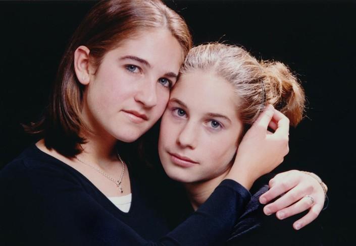 Sisters lovingly embrace during a studio portrait session.