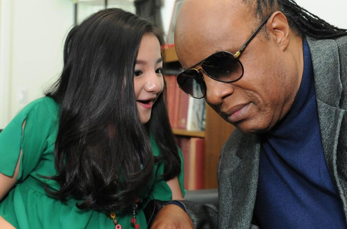 Singer/songwriter Stevie Wonder listens intently to a 16-year-old girl at the United Nations.