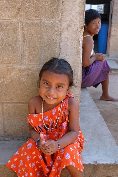 Yaqueline, a 4-year-old indigenous Wayuu girl, sits on the stoop of her home with her Aunt Edicta, behind her, in Maracaibo, Venezuela.