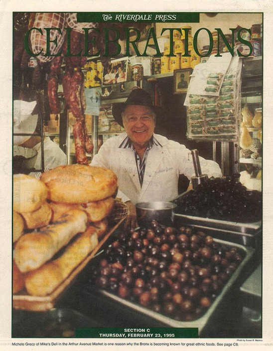 Tear sheet of Michele Greco, owner of Mike's Deli in the Bronx, standing behind his counter filled with freshly made bread, olives and sausages.