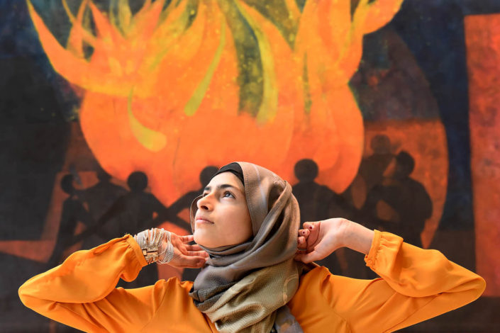 Minimill Sarfraz, 15, stands in front of a painted mural echoing the colors of her blouse, at UN Headquarters.