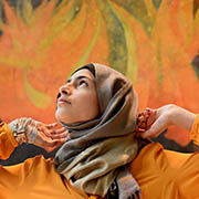Minahil Sarfraz stands with her arms gently raised, in front of a painted mural echoing the colors of her blouse, at United Nations Headquarters.