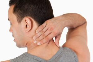 Young male massaging his back against a white background