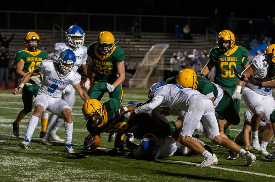 Senior running back Bryce Jackson jumps over an LHS defender at the football game Friday, Oct. 2. Photo by Ana Manzano.