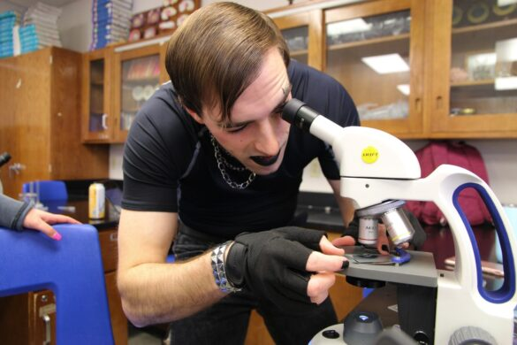 Biology teacher Mr. Sinclair examines brine shrimp under a microscope, adjusting the glass with painted nails and fingerless gloves. Drawing inspiration from Marilyn Manson, Sinclair went all out 90's goth with makeup and eyeliner.