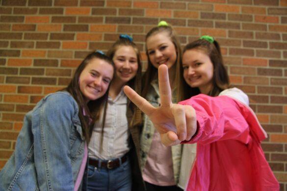 Seniors Maddie Orr, Greta Scheidt, Grace Dyer and Alexis Walker wear matching scrunchies, denim, and bright 80's colors.