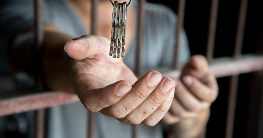 A prisoner getting handed the keys to his cell