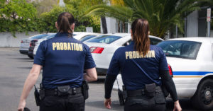 Two female probation police officers walking back to their squad car