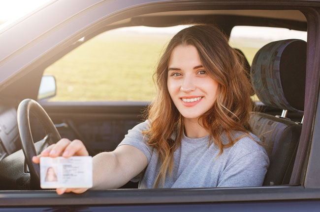 Woman smiling and presenting her driver's license