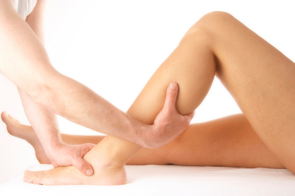 massage of a female calf muscle on white